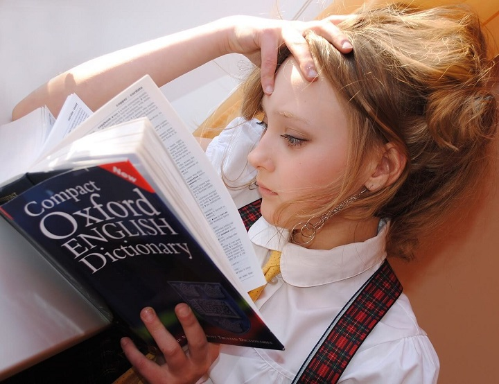 a girl is reading dictionary