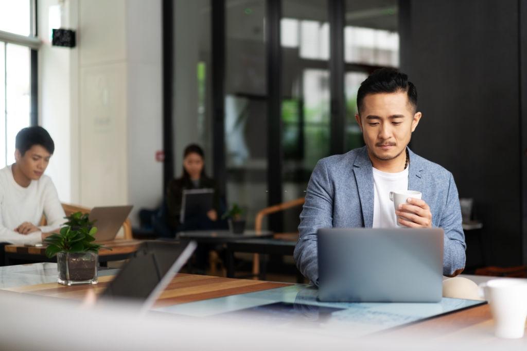 man sitting at cafe looking laptop