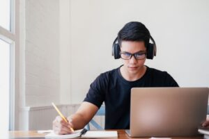 a male student wearing a headphone for online learning